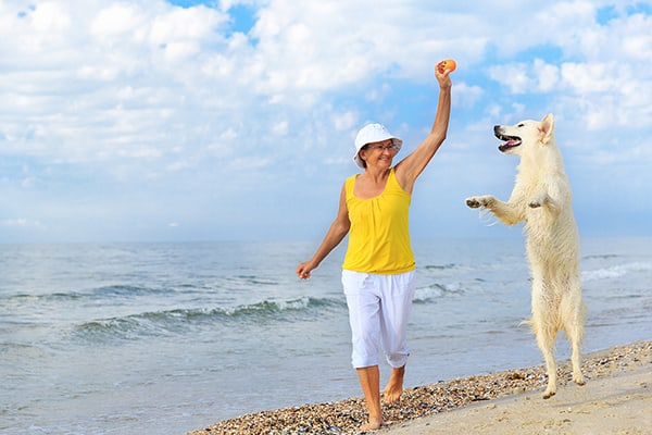 woman with dog on the beach